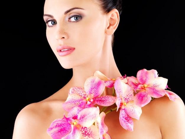 Schönes gesicht einer erwachsenen frau mit gesunder haut und rosa blumen auf körper - studio