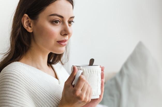 Schönes gesicht eines mädchens, sitzt ein mädchen in der weißen strickjacke auf einem sofa mit einer schale heißem tee in ihren händen