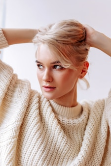 Schönes gesicht. junge attraktive blonde frau mit schönem gesicht, die zu hause ins fenster schaut