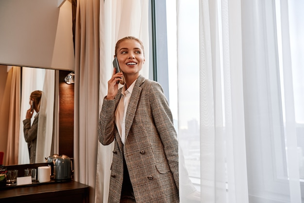 Schönes gespräch mit altem freund. junge und stilvolle geschäftsfrau mit smartphone, die in der nähe des spiegels im hotelzimmer steht und per smartphone spricht