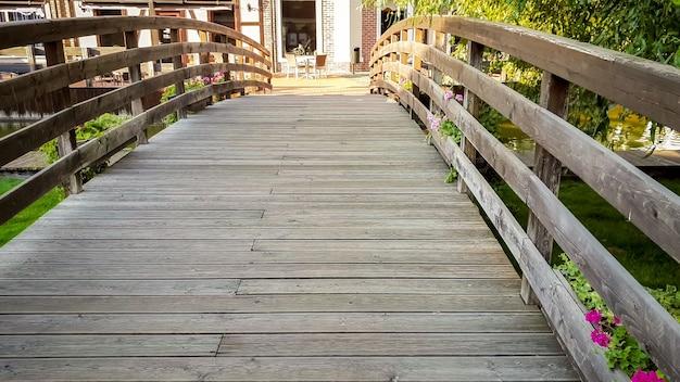 Schönes getöntes bild einer kleinen holzbrücke über den fluss in der europäischen stadt am hellen sonnigen tag