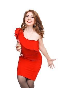 Schönes glamouröses mädchen mit roten lippen in einem intelligenten schwarzen kleid mit einem glas champagner lokalisiert auf einem weißen hintergrund, der die kamera betrachtet