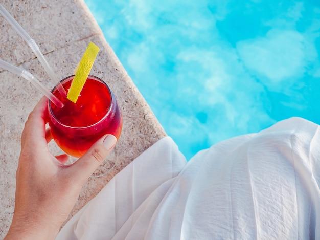 Schönes glas mit einem cocktail im pool. draufsicht