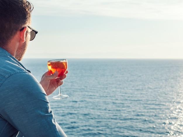 Schönes glas mit einem getränk auf dem hintergrund der meereswellen und der sonnenstrahlen. nahansicht. konzept von freizeit und reisen