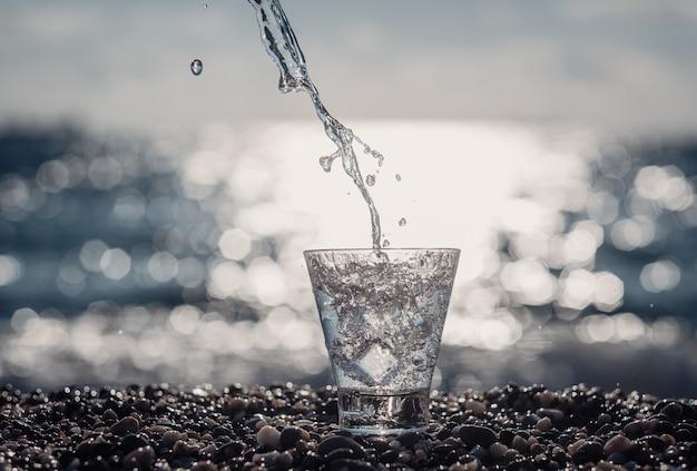 Schönes glas mit eis und reinem mineralwasser am meer.