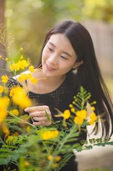 Schönes glückliches asiatisches modell der jungen frau draußen in einem wald. hübsches thailändisches mädchen im garten.