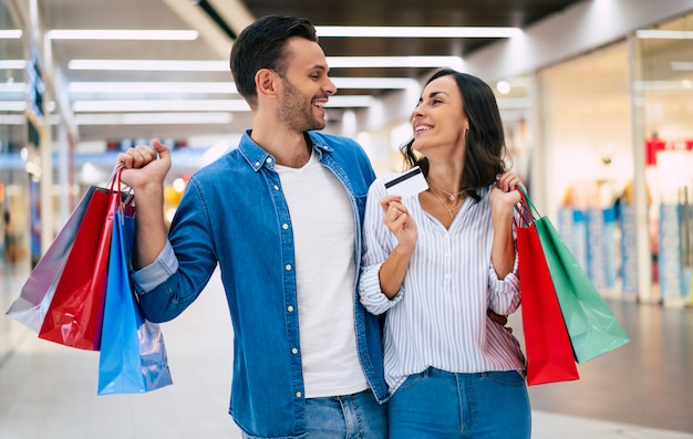 Schönes glückliches aufgeregtes aufgeregtes paar in der liebe oder in der familie mit papiertüten und kreditkarte in den händen beim gehen während des einkaufens im einkaufszentrum