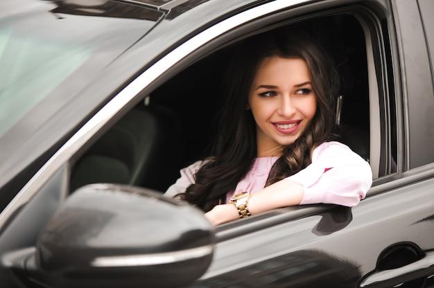 Schönes glückliches brünettes mädchen auf autofenster