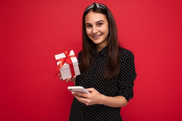 Schönes glückliches brunettemädchen lokalisiert über bunter hintergrundwand, die stilvolle freizeitkleidung trägt, die geschenkbox hält und kamera betrachtet.