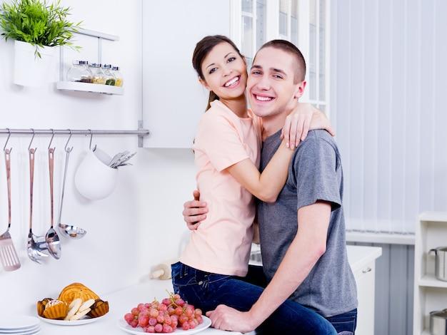 Schönes glückliches junges flirtpaar, das im kithen umarmt