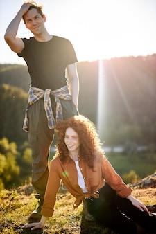 Schönes glückliches junges kaukasisches paar, das während des abenteuers in der landschaft der rothaarigen lockigen fe...