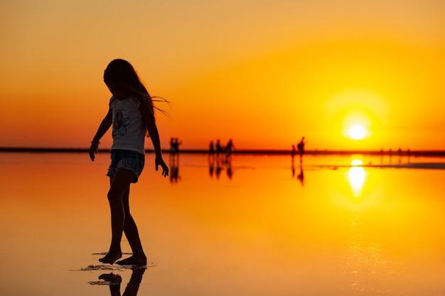 Schönes glückliches junges mädchen, das entlang des spiegelrosa salzsees geht, der die warme abendsonne genießt, die den feurigen sonnenuntergang und ihr spiegelbild betrachtet