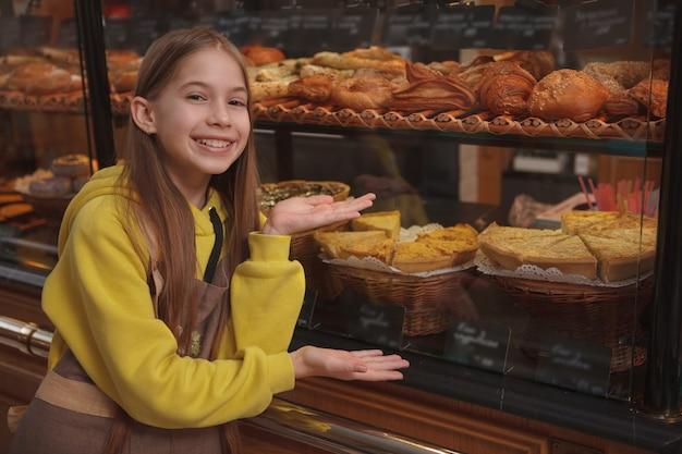 Schönes glückliches junges mädchen, das lächelt und auf einzelhandelsanzeige des bäckereigeschäfts zeigt