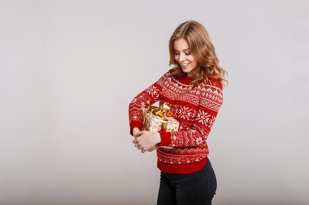 Schönes glückliches junges mädchen in einem roten weinlesepullover hält ein geschenk auf einem grauen hintergrund