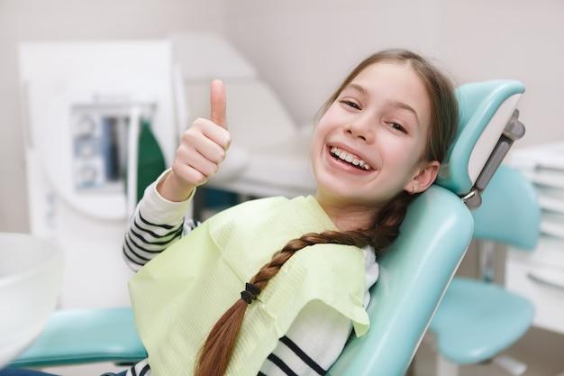 Schönes glückliches junges mädchen mit den lächelnden gesunden zähnen, die daumen hoch in der zahnklinik zeigen