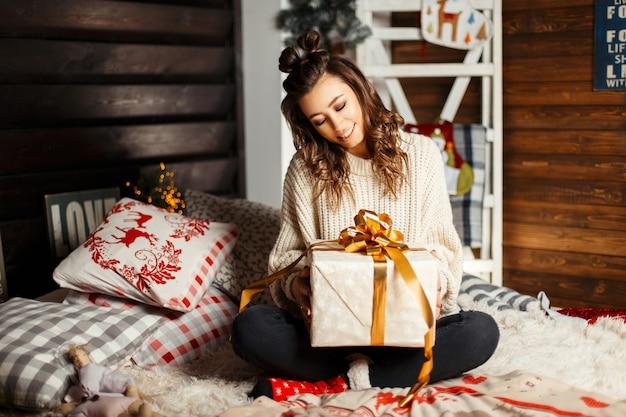 Schönes glückliches junges mädchen mit einem lächeln in einem gestrickten weinlesepullover mit einem geschenk auf dem bett am heiligabend