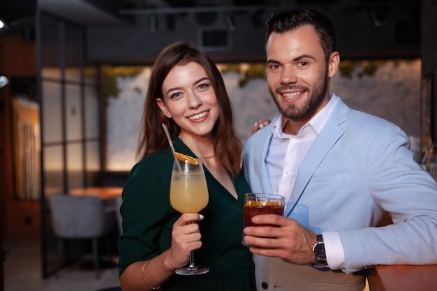 Schönes glückliches junges paar, das in die kamera lächelt und ihre cocktails im nachtclub hält