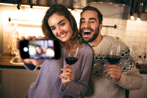 Schönes glückliches junges paar, das romantischen abend zusammen zu hause verbringt, rotwein trinkt, ein selfie macht
