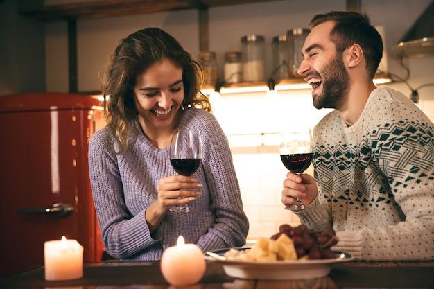 Schönes glückliches junges paar, das romantischen abend zusammen zu hause verbringt, rotwein trinkt, röstet
