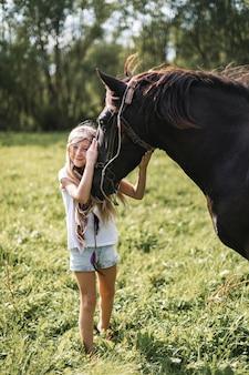 Schönes glückliches kaukasisches kindermädchen, das freizeitkleidung und boho-accessoires im haar trägt,