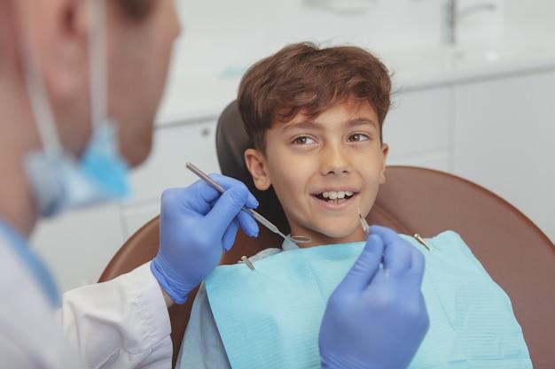 Schönes glückliches kind, das mit gesunden zähnen lächelt und seine zahnuntersuchung erhält