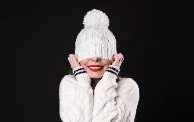 Schönes glückliches lächelndes mädchen, das ihre augen versteckt