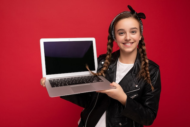 Schönes glückliches lächelndes mädchen mit brünetten zöpfen, das computerlaptop mit schwarzer jacke hält und