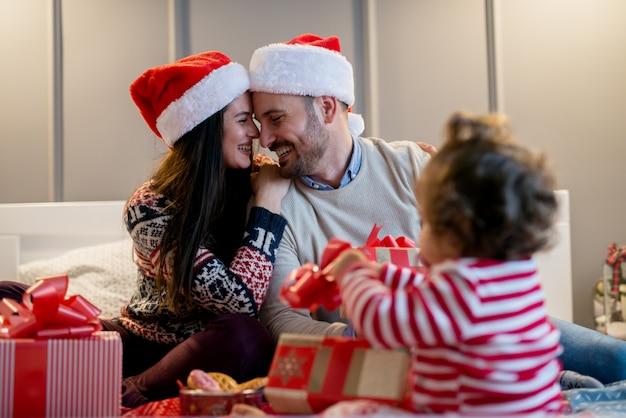 Schönes glückliches liebespaar, das für weihnachten umarmt, während ihre kleine tochter mit geschenken spielt.