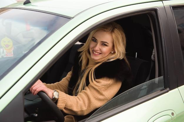 Schönes glückliches mädchen auf autofenster, junge frau, die ihr auto fährt