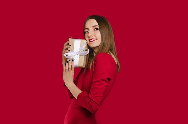 Schönes glückliches mädchen, das geschenkbox im roten kleid hält. valentinstag konzept