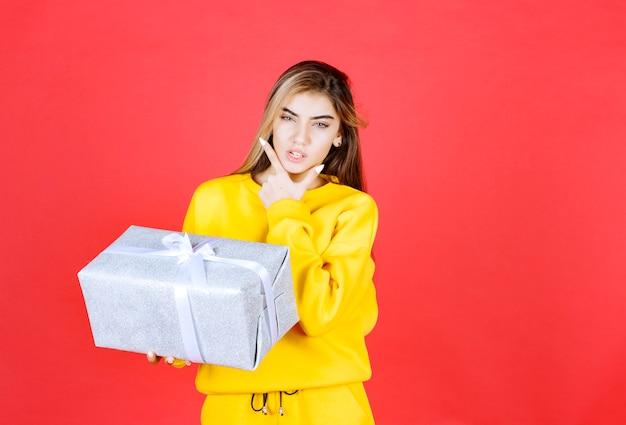 Schönes glückliches mädchen, das mit geschenkbox auf roter wand aufwirft