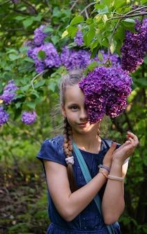 Schönes glückliches mädchen, das mit lila blumen bleibt