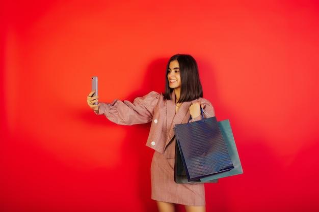 Schönes glückliches mädchen im roten modischen kleid macht selfie und posiert auf lokalisiertem rotem hintergrund.