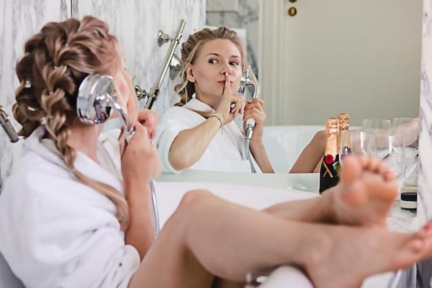 Schönes glückliches mädchen in einem bademantel, der spaß in der badewanne hat, die auf dem duschmischer wie am telefon spricht