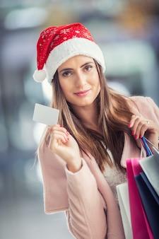 Schönes glückliches mädchen in weihnachtsmütze mit kreditkarte und einkaufstüten im einkaufszentrum