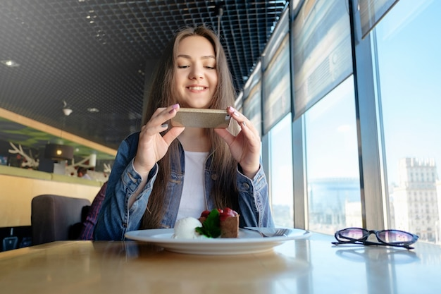 Schönes glückliches mädchen macht foto von essen im café, latte auf dem tisch, desserteis schokoladenkuchen kirschminze