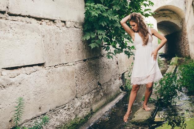 Schönes glückliches mädchen mit lockigem natürlichem haar im weißen kleid nahe grünen baumblättern