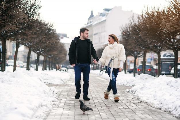Schönes glückliches mädchen und ihr hübscher freund, die zusammen auf die schneebedeckte straße des winters geht. neujahr und weihnachten.