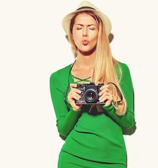 Schönes glückliches nettes blondes frauenmädchen in der zufälligen sommergrün-hippie-kleidung macht die fotos, die retro- fotoapparat halten und gibt einen kuss