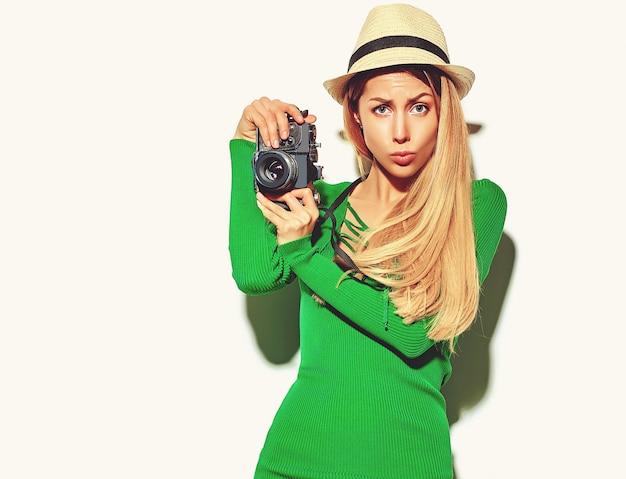 Schönes glückliches nettes blondes frauenmädchen in der zufälligen sommergrün-hippie-kleidung macht fotos, die retro- fotoapparat halten