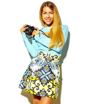 Schönes glückliches nettes blondes frauenmädchen in der zufälligen sommerhippie-kleidung macht fotos, die retro- fotoapparat halten