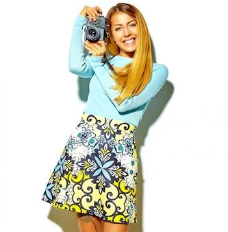 Schönes glückliches nettes blondes frauenmädchen in der zufälligen sommerhippie-kleidung macht fotos, welche die retro- fotokamera halten, lokalisiert auf einem weiß