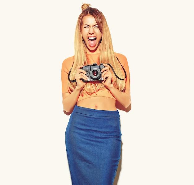 Schönes glückliches nettes blondes frauenmädchen in der zufälligen sommerhippie-kleidung macht fotos, welche die retro- fotokamera lokalisiert auf einem weiß halten