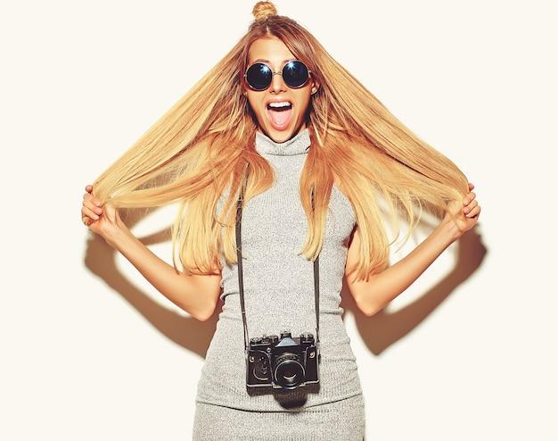 Schönes glückliches nettes blondes frauenmädchen in der zufälligen sommerhippie-kleidung macht fotos, welche die retro- fotokamera lokalisiert auf einem weiß mit dem haar in den händen halten