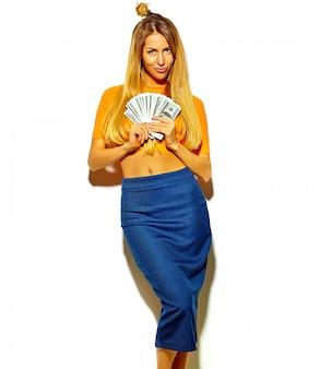 Schönes glückliches nettes lächelndes blondes frauenmädchen im zufälligen bunten hippie-sommer kleidet ohne das make-up, das dollarbanknoten hält