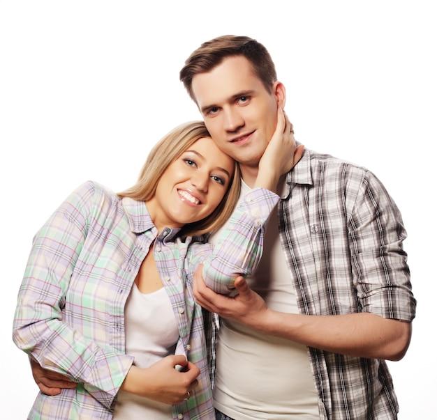 Schönes glückliches paar, das auf weiß umarmt.