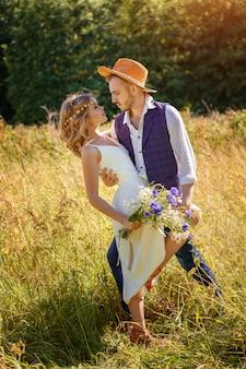 Schönes glückliches paar, das im sommer auf einem feld tanzt