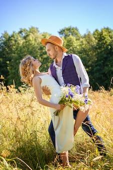 Schönes glückliches paar, das in einem feld im sommer an einem sonnigen tag tanzt.