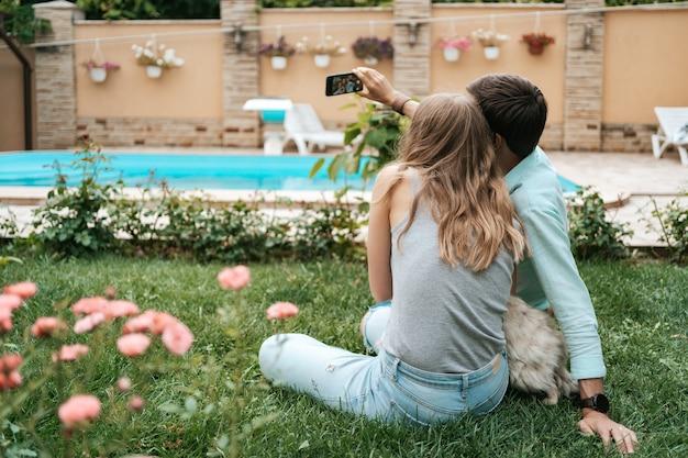 Schönes glückliches paar, das selfie mit ihrem schönen hund auf dem hinterhof macht, während auf dem gras sitzend
