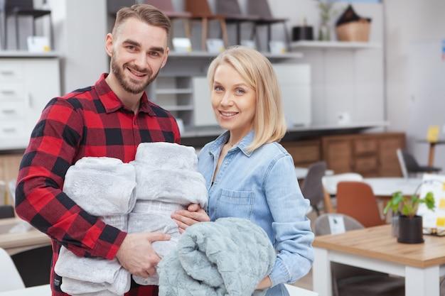 Schönes glückliches paar, das zur kamera lächelt und gemütliche weiche decken im haushaltswarengeschäft kauft